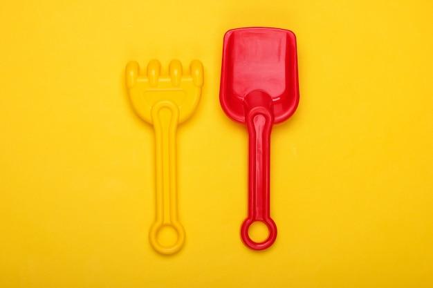 Kinder rechen und schaufel für einen sandkasten oder strand auf einem gelben
