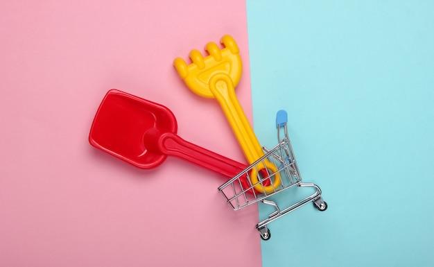 Kinder rechen und schaufel für einen sandkasten oder strand im einkaufswagen auf rosa blauem pastell