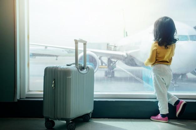 Kinder reisen konzept. rückseite eines zwei jahre alten mädchens, das auf einstieg wartet