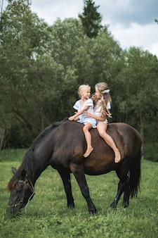 Kinder reiten pferd in den bergen