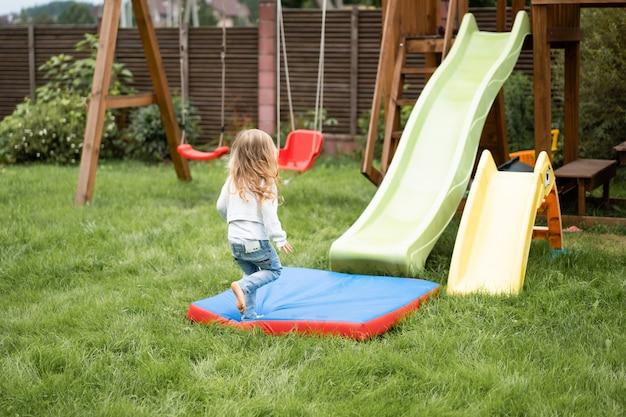 Kinder reiten von der kinderrutsche, schwestern spielen gemeinsam im garten