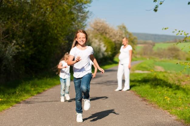 Kinder rennen einen pfad entlang, schwangere mutter steht