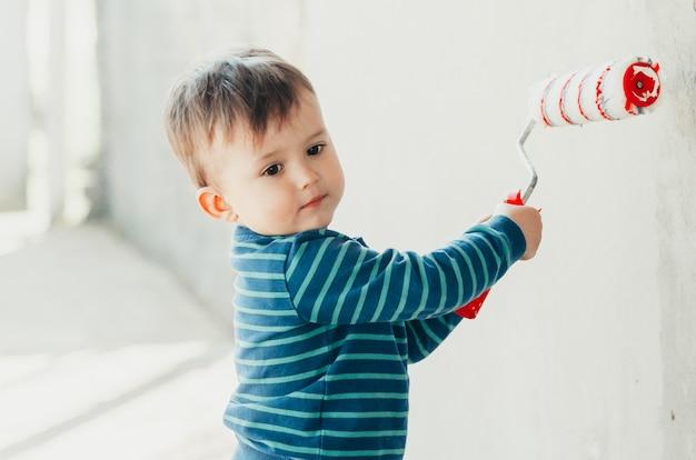 Kinder rotes kissen oder ein hausierer, um eine wand an der außenseite des hauses zu streichen