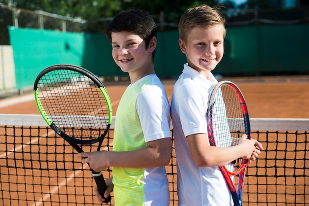 Kinder rücken an rücken auf dem tennisplatz