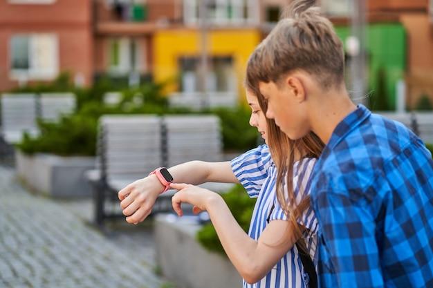 Kinder rufen ihre eltern mit rosa smartwatch in der nähe der schule an.
