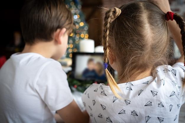 Kinder rufen sich per video an, um in der winterpause in kontakt zu bleiben. kleiner junge mit weihnachtsmütze sitzt vor dem computerbildschirm und chattet online mit einer gruppe seiner verschiedenen freunde am heiligabend zu hause