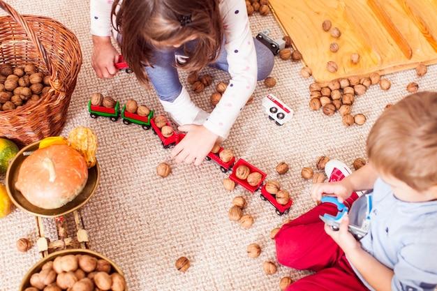Kinder sammeln nüsse in einer spielzeugeisenbahn und lernen im kindergarten auf dem boden sitzend zu zählen. güterzugkonzept