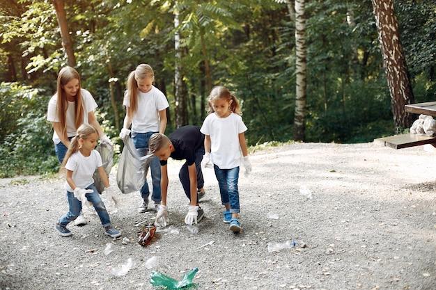 Kinder sammelt müll in müllsäcken im park