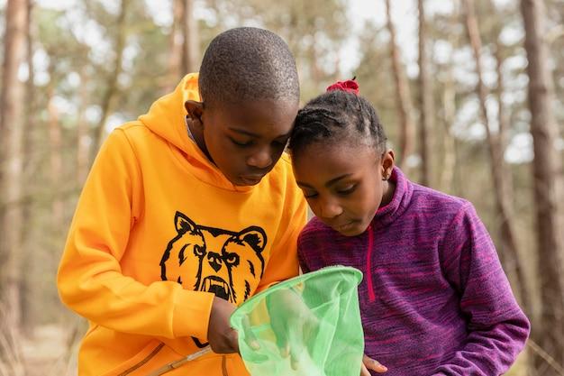 Kinder schauen durch ihre fischernetze