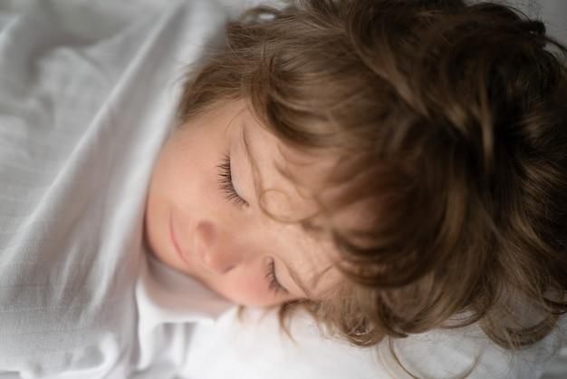 Kinder schlafen allein in einem bequemen bett mit weißer bettwäsche.