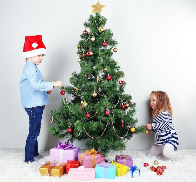 Kinder schmücken weihnachtsbaum mit kugeln im zimmer