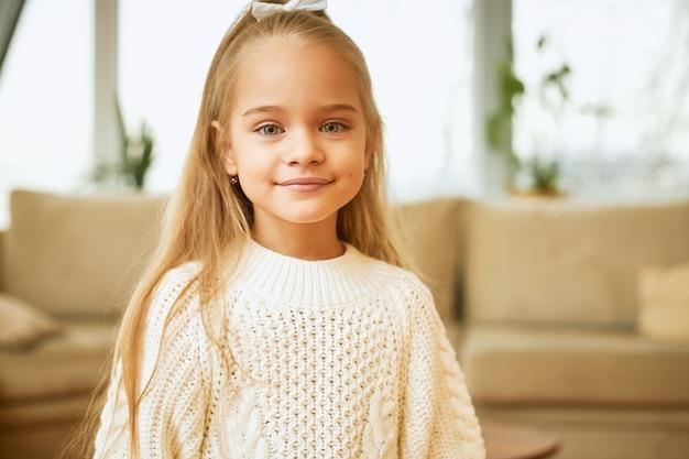 Kinder, schönheit und stil. schönes kaukasisches kleines mädchen mit den blauen augen, dem niedlichen lächeln und den langen haaren, die im wohnzimmer posieren, gekleidet im kuscheligen weißen pullover, in der guten laune, im freudigen blick