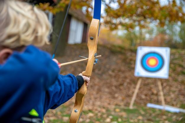 Kinder schossen während eines wettkampfs im bogenschießen im wald aufs ziel