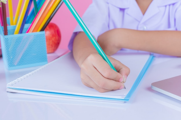 Kinder schreiben buchgesten auf einen rosa hintergrund.