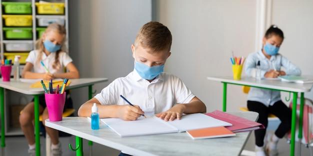 Kinder schreiben im klassenzimmer, während sie medizinische masken tragen