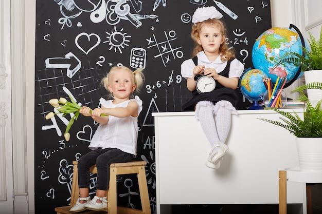 Kinder schüler lernen in der schule am ersten september, am letzten tag des studiums, den wechsel zwischen den lektionen. kinder der grundschule ruhen sich aus