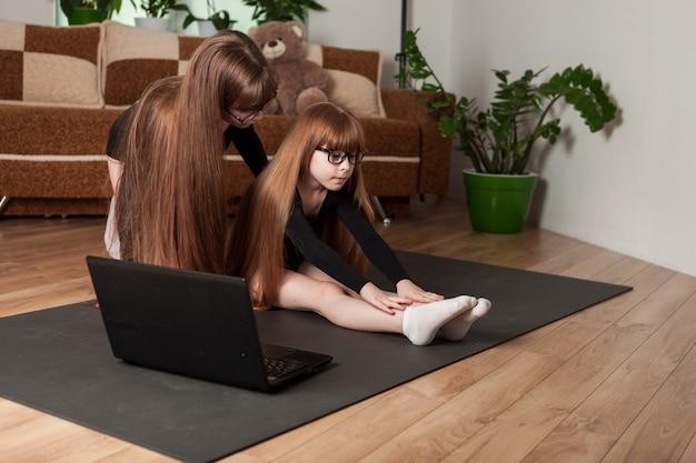 Kinder, schwestern, halten zu hause eine trainingseinheit auf der gymnastikmatte ab. mädchen in fitness-bodys sehen sich eine online-lektion auf einem laptop an und dehnen sich.