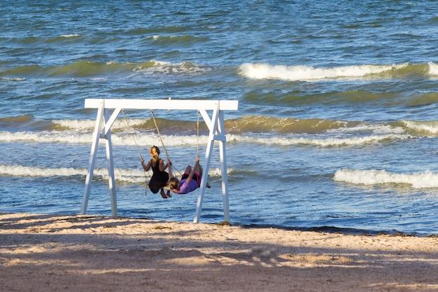 Kinder schwingen auf schaukel auf dem seeweg. schatten im sand. wellen auf see. algen am ufer.