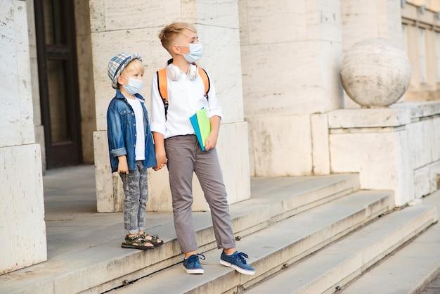 Kinder sind bereit, nach der quarantäne und sperrung von covid-19 zu lernen. kinder tragen gesichtsmasken. schüler der grundschule. gruppe von kindern in sicherheitsmasken zur vorbeugung von coronaviren.