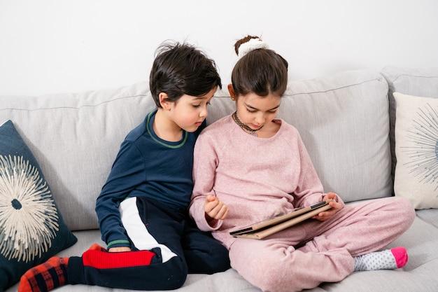 Kinder sitzen auf dem sofa und schauen in tablette