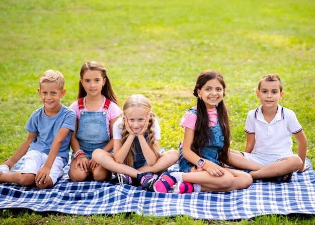 Kinder sitzen auf einer decke im park