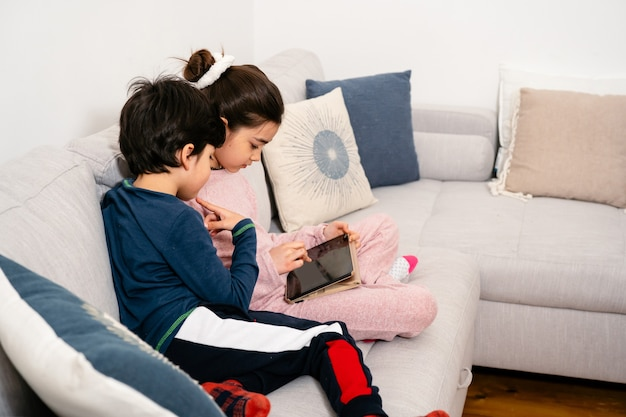 Kinder sitzen auf sofa mit tablette