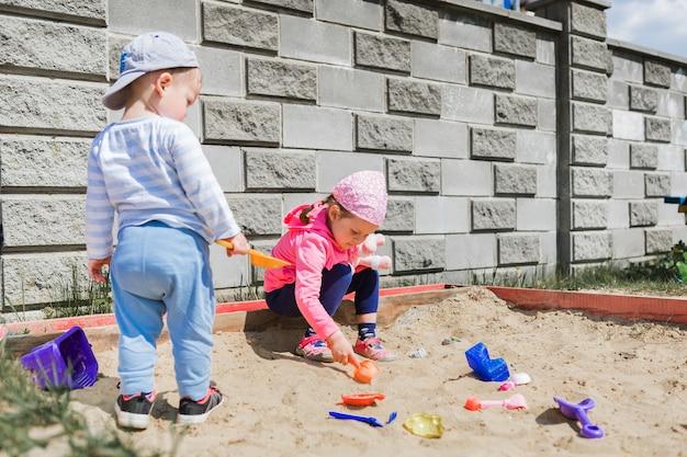 Kinder sitzen im sandkasten und spielen mit bunten plastikspielzeugen