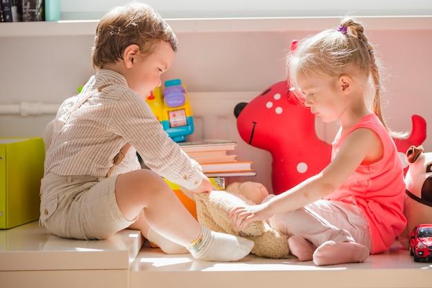 Kinder sitzen mit flauschigem spielzeug