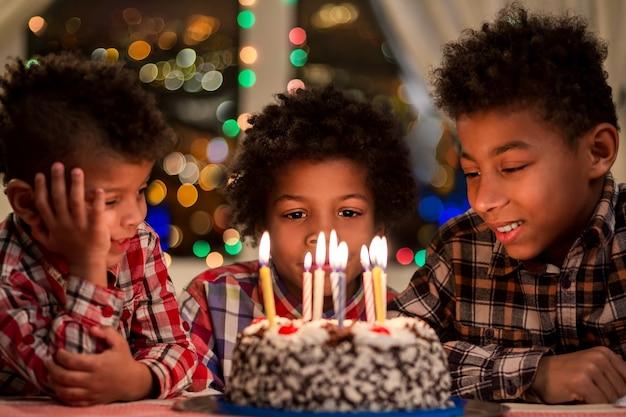 Kinder sitzen neben geburtstagstorte jungen in der nähe von kuchen mit kerzen geburtstagstisch neben fenster beeilen sich ...