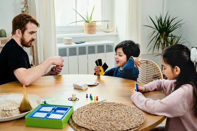 Kinder sitzen zusammen am tisch und spielen mit brettspiel