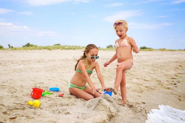 Kinder spielen am strand mit sand. mädchen bricht schloss aus sand, freundin schreit.
