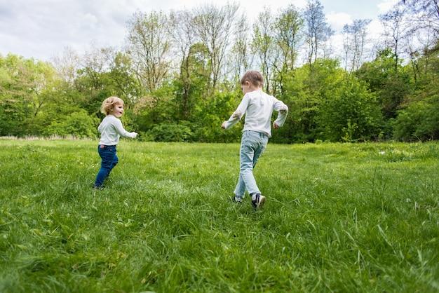 Kinder spielen auf dem grünen rasen im freien, laufen und haben spaß