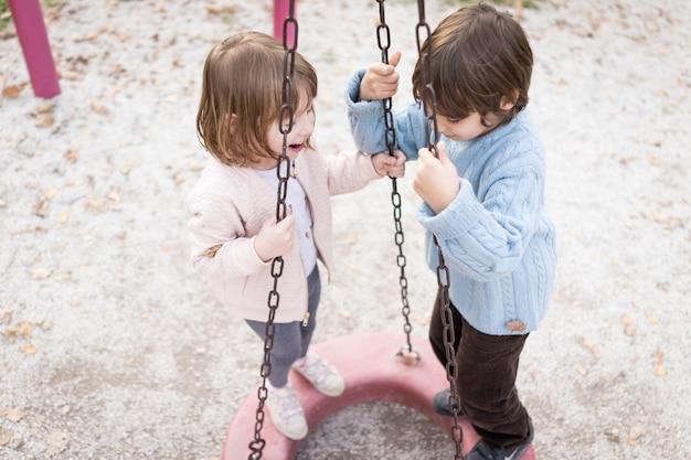 Kinder spielen auf dem spielplatz schwingen und rutschen