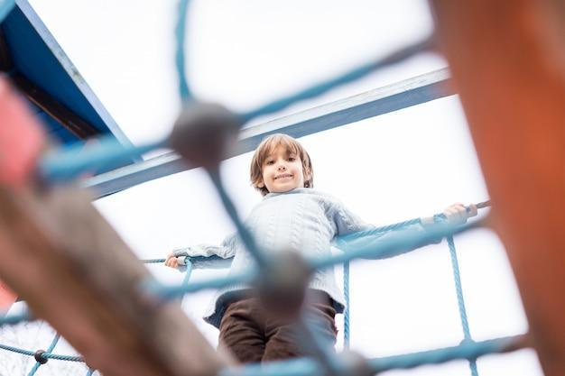 Kinder spielen auf dem spielplatz spazieren und klettern auf klettergerüsten