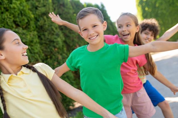 Kinder spielen. fröhlich lachende grundschulkinder, die an einem sonnigen tag im grünen park zusammen spielen