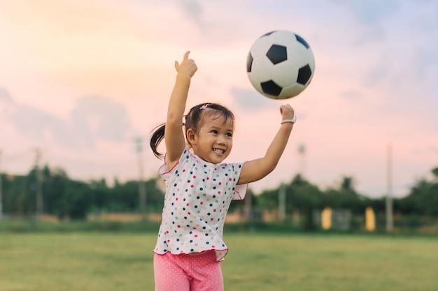 Kinder spielen fußball für die bewegung unter sonnenlicht