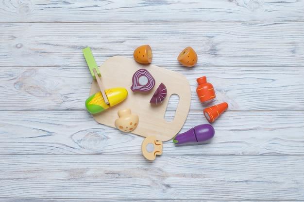 Kinder spielen holzgemüse. kinder entwickeln holzspiel. eine reihe von holzgemüse mit platz für text. plastikspielzeugküche für kinder. in scheiben geschnittenes spielzeuggemüse