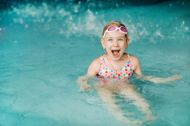 Kinder spielen im aquapark. kinder am wasserspielplatz des tropischen vergnügungsparks. kleines mädchen am schwimmbad. kind spielt am wasser. badebekleidung für junge kinder.