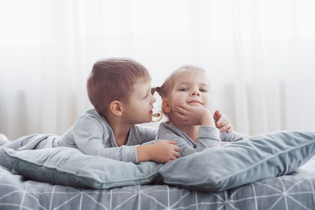 Kinder spielen im bett der eltern. kinder wachen im sonnigen weißen schlafzimmer auf. jungen und mädchen spielen im passenden schlafanzug. nachtwäsche und bettwäsche für kinder und babys. kindergarten interieur für kleinkind. familienmorgen