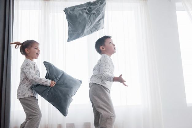 Kinder spielen im bett der eltern. kinder wachen im sonnigen weißen schlafzimmer auf.