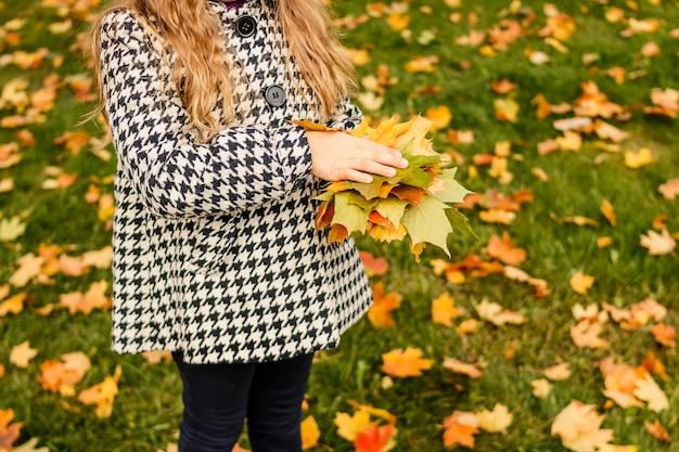 Kinder spielen im herbst park. kinder werfen gelbe und rote blätter. kleines mädchen mit ahornblatt. herbstlaub. familienspaß im freien im herbst. kleinkind kind oder vorschulkind im herbst.