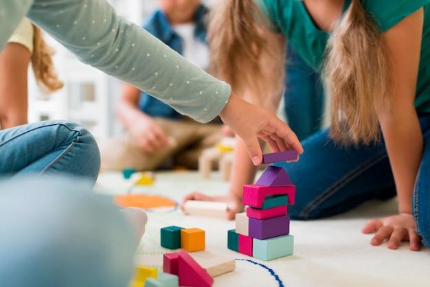 Kinder spielen im kindergarten mit turmspiel
