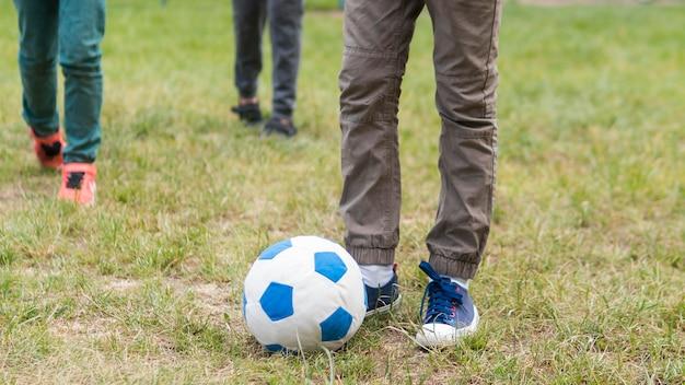 Kinder spielen im park mit fußball