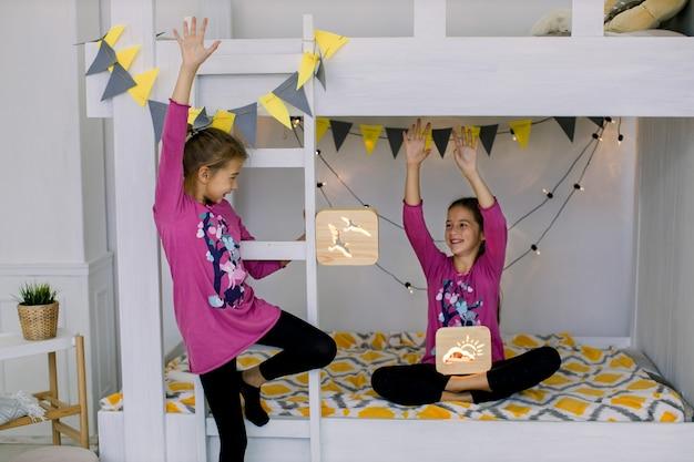 Kinder spielen im schlafzimmer. zwei lustige glückliche mädchen 10 jahre alt, schwestern im bunten pyjama, die spaß auf einem etagenbett haben, hölzerne nachtlampen halten.