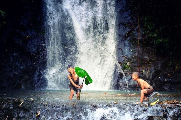 Kinder spielen im wasserfall