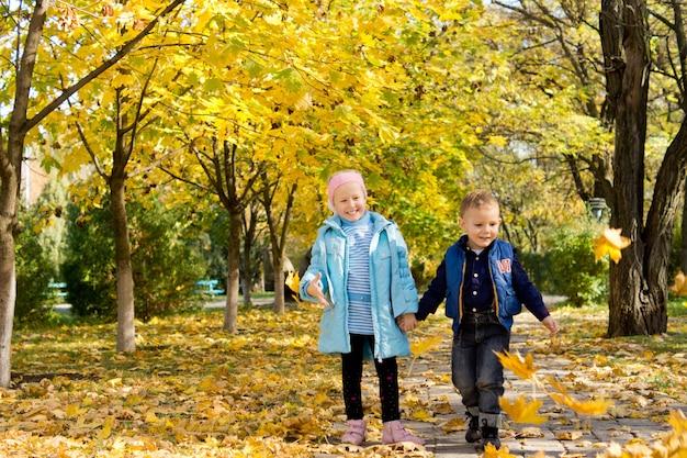 Kinder spielen im wind mit bunten gelben herbstblättern