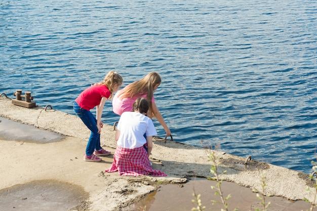Kinder spielen in der nähe des flusses am stadtufer