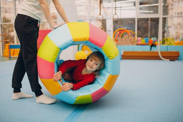 Kinder spielen in der turnhalle im kindergarten oder in der grundschule. kindersport- und fitnesskonzept.