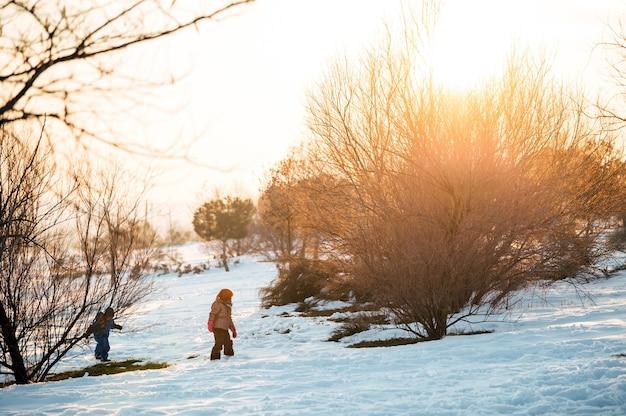 Kinder spielen in schneebedeckter landschaft