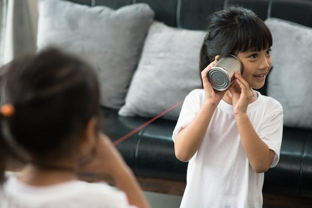 Kinder spielen mit blechdose und schnurtelefon als kommunikationskonzept